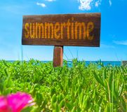 Summertime written on a wooden sign Royalty Free Stock Images