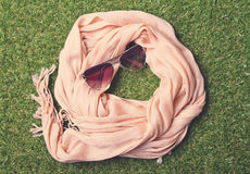 Summery pastel scarf and sunglasses on grass. Overhead view of fashion scarf and sunglasses on grass Royalty Free Stock Photo