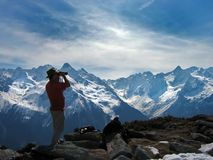 Summit. Man looking at alpine panorama with binoculars stock image