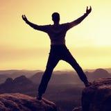 Summit achievemnt. Hiker in black celebrate triumph Stock Image