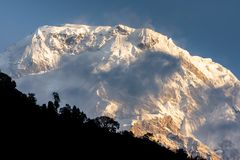 Summit of Annapurna South surrounded by clouds in the Himalayas royalty free stock image