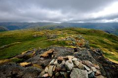 Dark storm clouds over the Helvellyn mountain range. The summit cairn of calf Crag stock photos