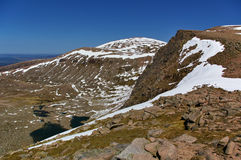 The summit of Cairn Gorm with valley, rocks, snow, lakes. The summit of Cairn Gorm with valley, steep slopes, rocks, snow, lakes below Royalty Free Stock Images