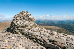 Summit cairn on the Old Man of Coniston in the Lake District. Summit cairn on the top of Coniston Old Man in the English Lake District.  The view of the Royalty Free Stock Photography
