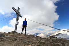 Summit cross and male mountaineer on mountain Weissspitze with panorama in Hohe Tauern Alps Stock Photo
