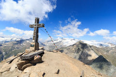 Summit cross and prayer flag on mountain Kreuzspitze with glacier panorama and Grossvenediger, Hohe Tauern Alps, Austria Royalty Free Stock Image