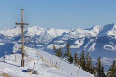 Summit cross in winter with outlook to a mountain range. Stock Photography