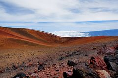 The summit of Mauna Kea, a dormant volcano on the island of Hawaii. Stunningly beautiful red stone peak hovering above clouds, the. Highest point in the state Stock Image