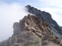 Summit of mountain in clouds. Rocky summit of high alpine mountain in clouds Royalty Free Stock Photos