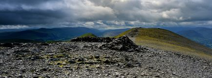 The summit shelter of Skiddaw. Storm clouds approaching Skiddaw summit Stock Photo