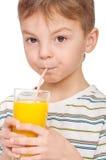 Sumo de laranja bebendo do rapaz pequeno fotografia de stock