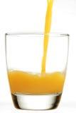 Sumo de laranja de derramamento no vidro Fotografia de Stock Royalty Free