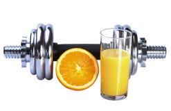 Sumo de laranja e dumbbel frescos Imagem de Stock