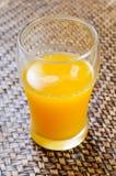 Sumo de laranja em um vidro no bambu tecido Fotografia de Stock Royalty Free