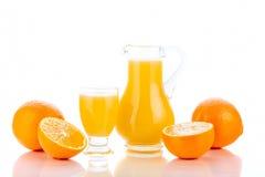 Sumo de laranja no jarro e nas laranjas fotografia de stock