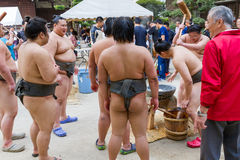 Sumo Wrestlers Making Mochi. FUKUOKA, JAPAN - NOVEMBER 6, 2016: A group of junior sumo wrestlers pound rice with a wooden mallet in the traditional manner to stock images
