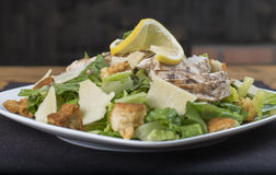 Sumptuous Gluten Free Chicken Caesar Salad. A sumptuous gluten free chicken Caesar salad on a black place mat.  The view is from the side Stock Photo