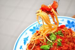 Sumptuous looking spaghetti. Close up shot of sumptuous looking vegetarian spaghetti on an Asian styled plate with fork picking up a mouthful Stock Photography