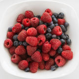 Sumptuous Raspberries and Blueberries In A White Dish Stock Photos