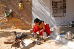 SUMRASAR,古杰雷特,印度- 2013年12月19日:准备thali印地安食物的妇女在一个房子的庭院里在Sumrasar,地方v 免版税库存图片