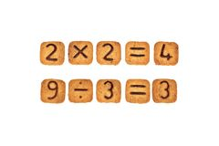Sums made of square cookies with chocolate numerals on them. Isolated on white background. Idea of funny and easy math learning during eating. Flat lay. Top royalty free stock image