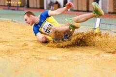SUMY, UCRÂNIA - 17 DE FEVEREIRO DE 2017: Serhiy Nykyforov que executa seu salto longo na qualificação na trilha interna ucraniana Imagens de Stock