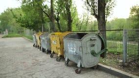Sumy, Ucrânia - 4 de maio de 2018: Escaninhos de lixo com lixo antes da cerca na rua na cidade filme