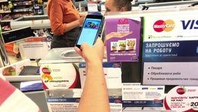 SUMY, UCRANIA - 13 DE AGOSTO DE 2018: Cliente que paga con paga de la manzana por el teléfono móvil en el terminal almacen de video