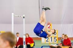 SUMY, UCRANIA - 28 DE ENERO DE 2018: Los triunfos de Vadym Kravchuk en la competencia del salto de altura en atletismo interior u Fotos de archivo