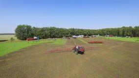 Sumy, Ucrania - 12 de septiembre de 2017: antena del tractor rojo que separa los fertilizantes artificiales en campo arado metrajes