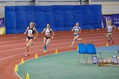 SUMY UKRAINA - FEBRUARI 17, 2017: idrottskvinnor konkurrerar i kvinna`en s 400m som kör i en inomhus friidrotthändelse Fotografering för Bildbyråer