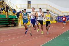 SUMY UKRAINA - FEBRUARI 17, 2017: idrottsmän som kör kvalifikation, springer i man`en s 400m som kör i ett inomhus spår och Royaltyfri Fotografi