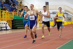 SUMY UKRAINA - FEBRUARI 17, 2017: idrottsmän som kör kvalifikation, springer i man`en s 400m som kör i ett inomhus spår och Arkivfoton