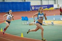 SUMY UKRAINA - FEBRUARI 17, 2017: Viktoria Grynko #129 och Yulia Shulyar #1218 konkurrerar i kvinna`en s 400m som kör Royaltyfria Bilder