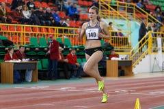 SUMY UKRAINA - FEBRUARI 17, 2017: Viktoria Tkachuk #140 spring i kvinna`en s 400m som kör i ett inomhus spår och Royaltyfria Foton