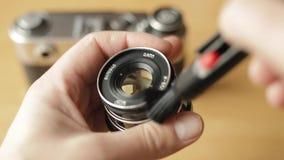 SUMY UKRAINA, MAR, - 09, 2018: Zbliżenie fotografa ` s wręcza starego rocznika obiektyw czysty przy kątem z pomocą a zbiory
