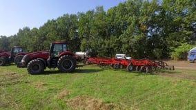 Sumy Ukraina - September 12, 2017: röda traktorer och bruka maskinerianseende på kanten av det gröna fältet stock video