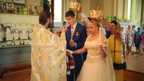 SUMY, UKRAINE - AUG 15, 2016: Newlyweds drinks wine from the hands of a priest. SUMY, UKRAINE - AUG 15, 2016: A young couple drinks wine from the hands of a stock video