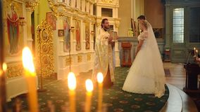 SUMY, UKRAINE - AUG 15, 2016: The priest with an icon in his hands gives a farewell to the newlyweds. Burning candles in the foreground stock video