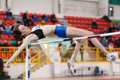 SUMY, UKRAINE - FEBRUARY 17, 2017: young sportswoman jumping over bar in qualification High Jump competition of Stock Photo