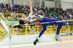 SUMY, UKRAINE - FEBRUARY 18, 2017: Yuliya Chumachenko jumping over bar in final High Jump competition of Ukrainian Royalty Free Stock Photo