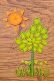 Sun, árbol y flores hechos del puerro y de rebanadas de la zanahoria en fondo de madera de la tabla de cortar Fotografía de archivo