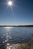 Sun über See mit Objektiv-Aufflackern Stockbild