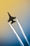 Into the sun. Aerobatic military jet in an abstract gradient sky leaving a smoke trail Royalty Free Stock Images