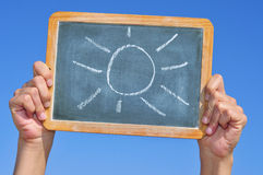 Sun. Someone holding a blackboard with a sun drawn in it Royalty Free Stock Photo