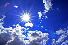 Sun. A blue sky with the sun and a few clouds with the airplane Royalty Free Stock Photos