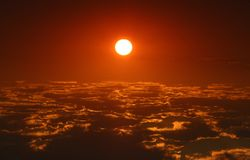 Sun above clouds. Dark red sun above clouds in morning stock photo
