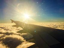 SUN ABOVE THE CLOUDS IN FLIGHT royalty free stock photography