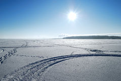 Sun above frozen lake in winter Royalty Free Stock Photo