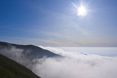 Sun above the hills. Sun on bright sky above the hills covered in clouds royalty free stock photo